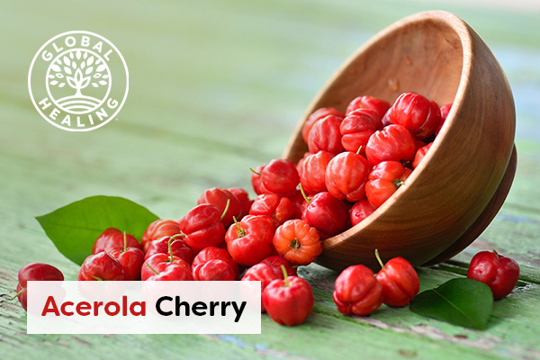 A wooden bowl on its side with bright red Acerola cherries pouring over a wooden tabletop.