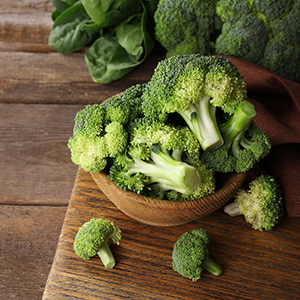 A bowl of Broccoli in a wooden bowl over a wooden tabletop with other green vegetables in the background.