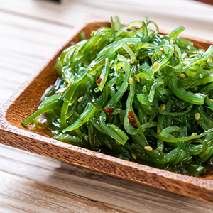 A bowl of organic seaweed salad in a wooden bowl.