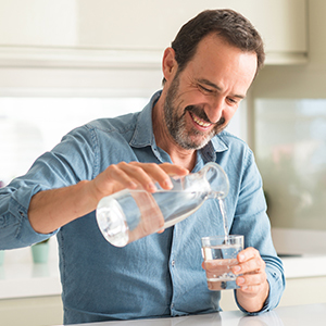 A man pouring water from a jug to a cup in a kitchen setting.