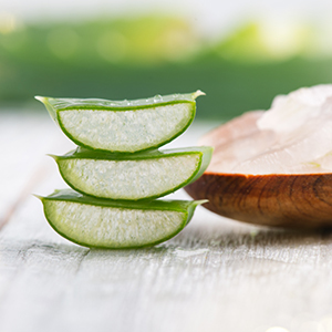 Sliced aloe vera with a wooden bowl in the background.