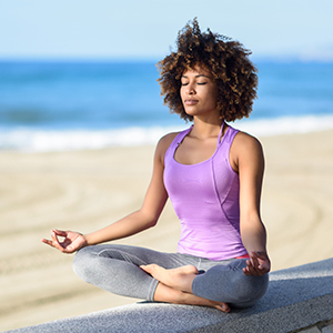 A woman in lotus meditation position with sand and beach in background.