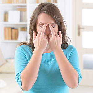A woman in a blue blouse holding her fingers to her eyes in a home setting.