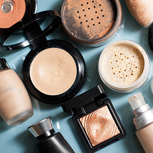 A variation of makeup and brushes laid over a light blue background.
