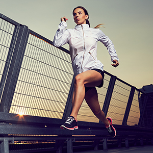 A woman running along a metallic rail with at sunrise.