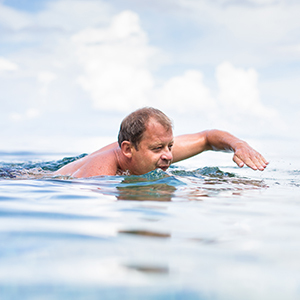 A man swimming in blue water on a sunny day.
