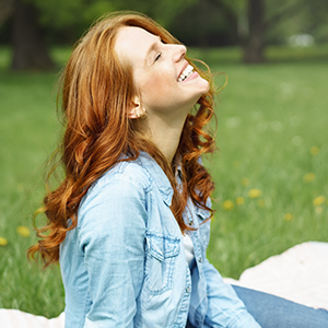 A woman with long hair sitting in an open field surrounded by trees while looking up and smiling