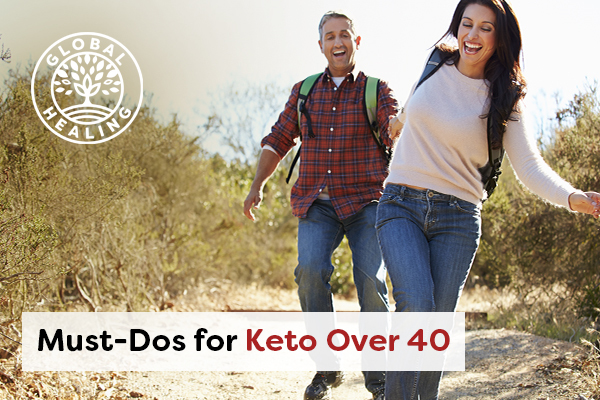 A couple laughing and holding hands while hiking down a dirt road.