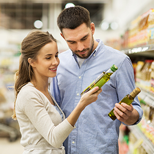 A young couple in a grocery store setting viewing nutrition facts for olive oil products.