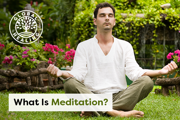 A meditating man sitting in an open green space with eyes closed.